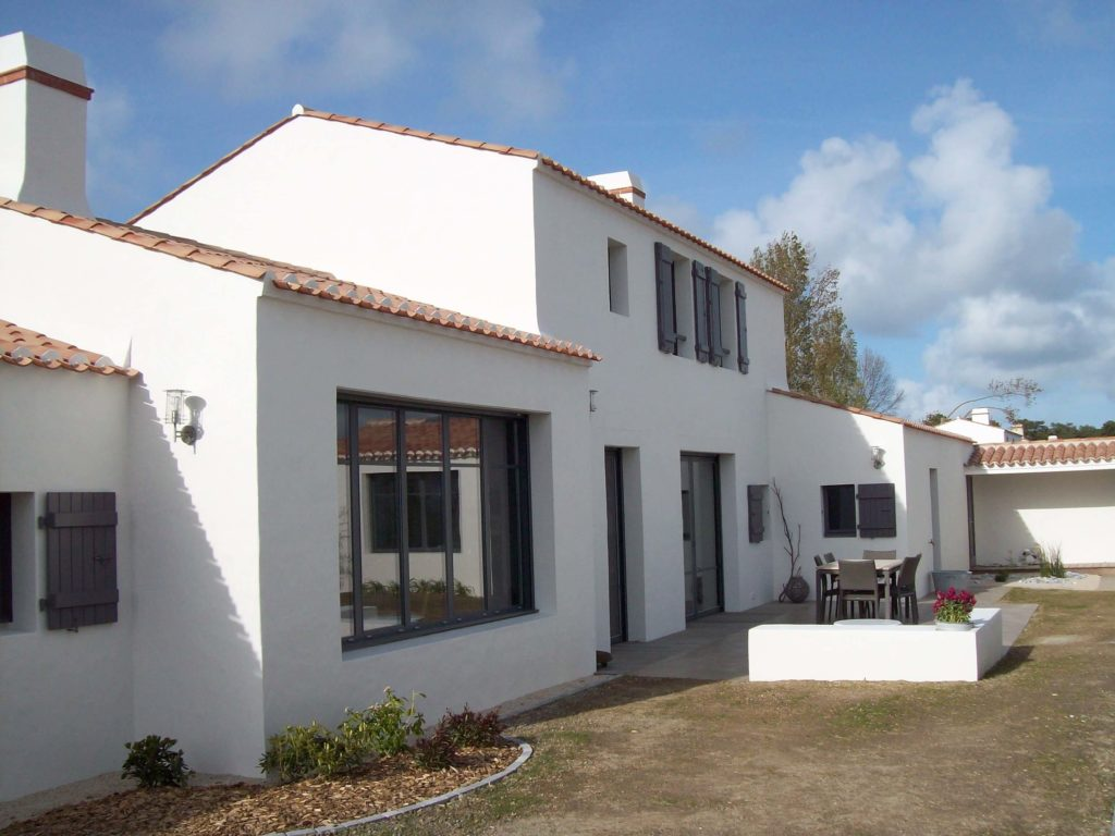 Maison en bord de mer blanche avec toiture en tuiles